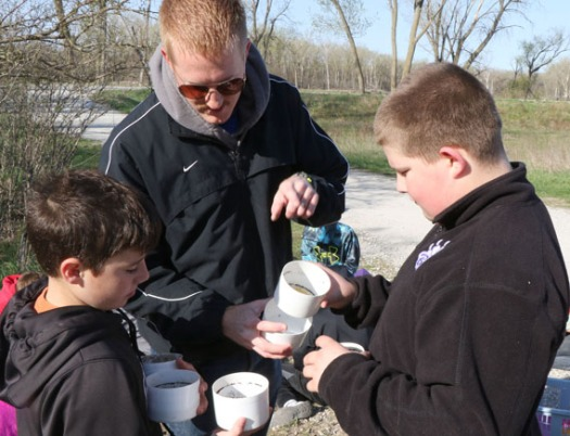 Gabe Gaskil and Kellen Hartzell with Mr. Norine take apart a sieve set  used to filter soil particles.