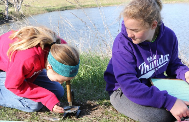 Carley Damme and Carmen Warrick study  soil samples . under a microscope.