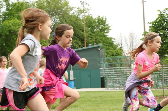 Eliza Finken and Kate Wulf, and Jordyn Slagle  race toward the finish line. fFrst grade fun day