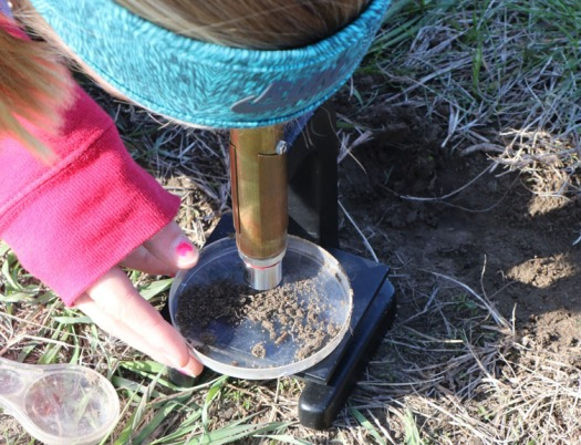 Carley Damme examines a soil sample with a telescope.