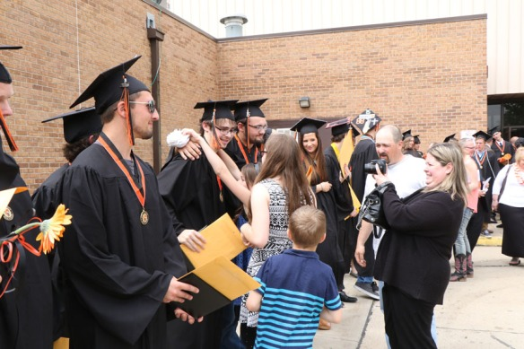 Graduates receive congratulations from family and friends following graduation ceremony.