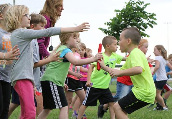 Jaxon Ellis hands off the baton to Lena Christensen.  during relay at first grade fun day