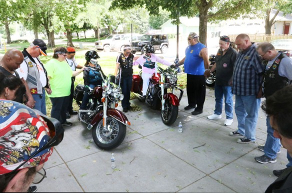 In foreground from left, Rose Hathaway and Beth Slovinski from Omaha join hands with  CMA  members in bike blessing.  CMA members Greg Casey and Paatty Maring in background.