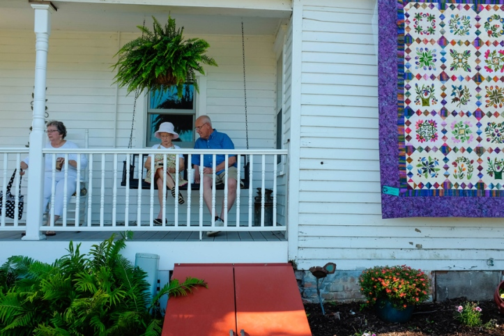 Judy Andersen,and Karen and Ken Sorensen find some shade and a breeze on the porch of Teri and Doug's home during the Quilts in the Country quilt show and garden tour.