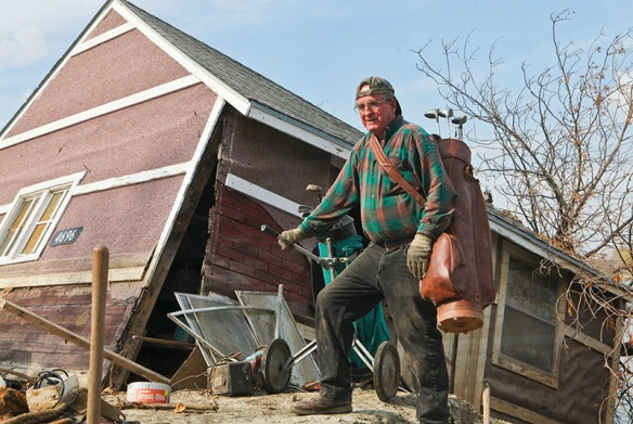 Harvey Palmer retrieves sets of golf clubs from his shed. His house is gone.