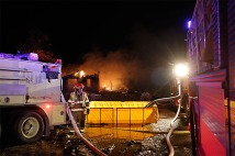 Pumper trucks fill a portable reservoir while fighting a house fire near Fontanelle NE.
