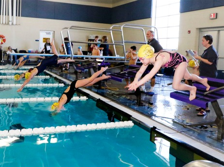 Foreground to back, Lainey Bilau Jane Busoom, Aubrey Lefeber, and Bella Roche dive in at the start of the Girls 8 and under 25 Freestyle.