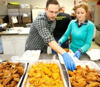 Judd and Ariana Bauer prepare fish dinners to go. The Bauers just recently moved to Fort Calhoun from Omaha.