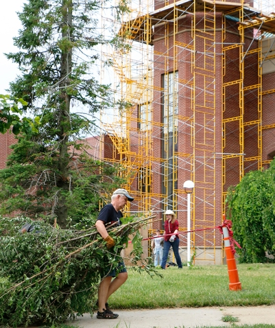 Bill Henderson drags an arm load of limbs cross the Durham center lawn.