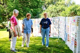 Quilter Darlene Harper with friends Wilma Kanter, and Florence Renner roll along a display of quilts.