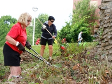Diane Christenson and Karen Riddle clean up flower beds near the Durham Center. Dana College cleanup