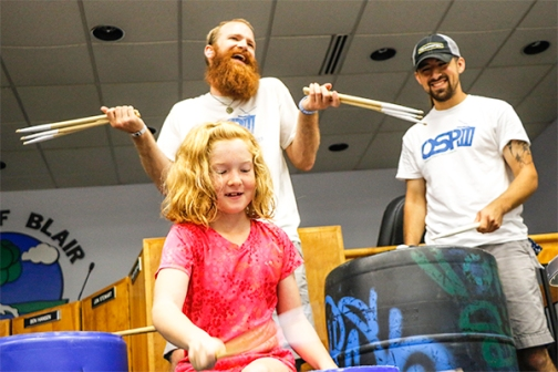 Chris Sikkema and Josh (Smallz) Meyer watch as Hannah Heuton plays the trash can drums with the Omaha Street Percussion