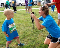 Blair physical education teacher Kim Leggott is ready with a medal for 5 year old Ryker Mandarich as he finishes his first Triathlon.