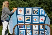Krista Bendell places a name tag on a quilt made by her grandmother, Darlene Haper, for Krista's brother when he graduated from Arlington High School. Krista is the daughter of Quilts in the Country hosts Teri and Doug Wolfe.