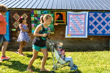Lilly Lang pushes her younger sister Lilly in the stroller with Mom Lori and sister Savannah Lang in the background. Quilts in the Country quilt show and garden walk