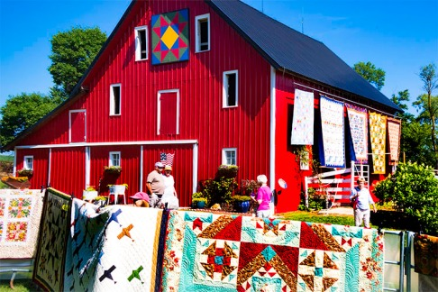 Visitors stroll though farmyard and gardens filled with quilt displays.