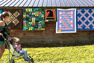 Lilly Lang pushes her younger sister Lilly in the stroller past a display of quilts.