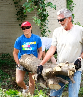 Tammy Reeh and John Mark Nielsen carry tree truck to refuse pile.