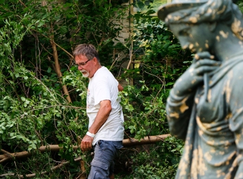 Tom Jackson removes brush from Letha's Garden.