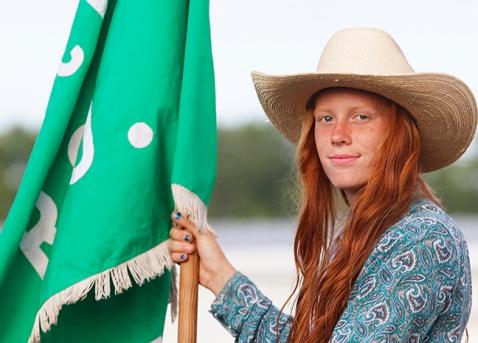 Lauren Schwedhelm carries McKay Rodeo banner in opening ceremony Friday evening.