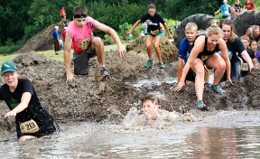 A mass of competitors race toward the mud pit at the Cowboy 5K Saturday.