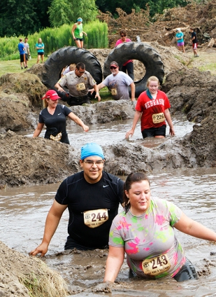 Competitors wade through the muddy water pits.
