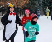 Tesssa Rutledge in penguin costume, Avery McKennan and Blake Welchert run through Fort Atkinson during The Holiday Fun Run during Christmas in Calhoun.