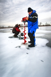 Mitch Cates uses an auger to drill a new hole in the ice while Taylor Herman scoops slush out of another fishing hole.
