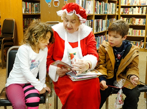 Lucy and Quinn Billsbach attentively listen to Mrs. Claus read a story at the Fort Calhoun library. Story time with Santa and Mrs. Clause was one of many popular Christmas in Calhoun.events on Saturday.