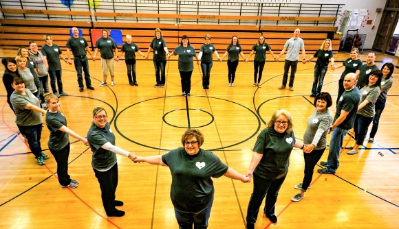 Arbor Park Intermediate School Facultyand staff stand in the shape of a heart in the school's gym. The educators are wearing T-shirts in honor or reading teacher Kris Burns, who died suddenly of heart failure in September. The teachers purchased the T-shirts or made donations which will be given to the American Heart Association in Burn's name.