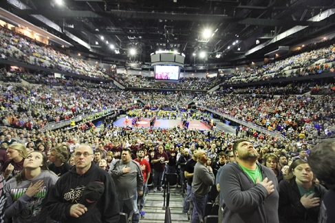 Spectators and wrestlers stand facing the American flag during the playing of the Star Spangled Banner at Century Link Center in Omaha.
