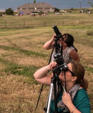 Julie Sterling- Baldauf and Gigi DesRosiers look through cameras to capture solar eclipse images near Wymore, NE, August 2017