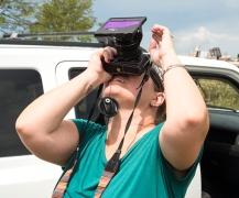 Solar filter hack: Gigi DesRosiers looks through dark glass from welding helmet covering her camera lens.