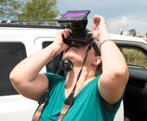 Solar filter hack: Gigi DesRosiers looks through dark glass from welding helmet covering her camera lens.