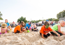 Kids build sand castles and search for treasure in a gigantic sand pile at the FC Parking lot party Saturday.