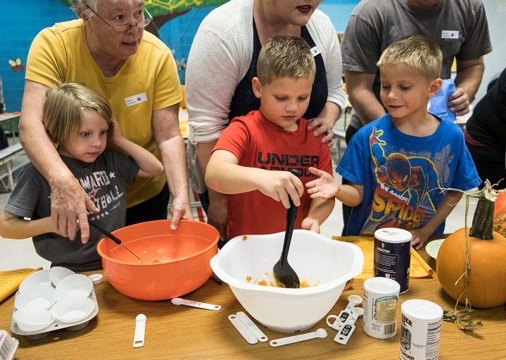 Second graders stir a batch of pumpkin muffins. Pumpkin Fun South School.