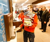 Christopher Gibbons-Christie returns a staack of books he checked out at the old library. Blair Library Grand Opening