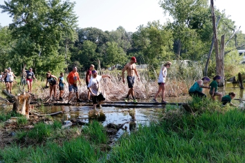 Competitors balance along logs across a stream Saturday during the Cowboy 5 K. Washington County Fair Saturday AM