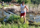 Veteran mud run competitor Drew Harsin leaps across the wetlands on the way to his first place finish at the Cowboy 5 K. Washington County Fair Saturday AM