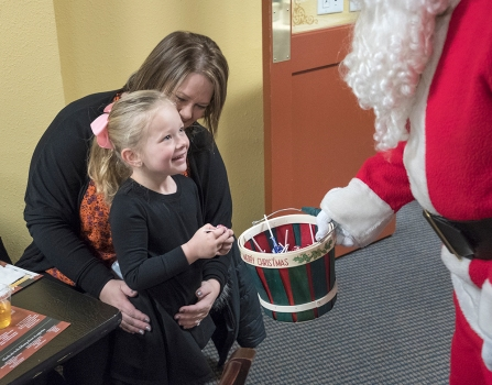 Ellie Schrad with mother Angie thanks Santa for the sucker at Christmas for the Coat Wednesday at Fernando's Cafe and Cantina.