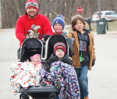 Rance and son Aden Johnson with Quinn Billesbach pus cart wit Amelia and Carter Johnson during the Fort Calhoun Holiday Sweater Fun Run.