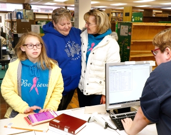 Last checkout in the old library. Taylor Bergmeyor is the last person to check out books in the old library while her grandmother Janice Vonheim talks with librarian Gail Roberts.