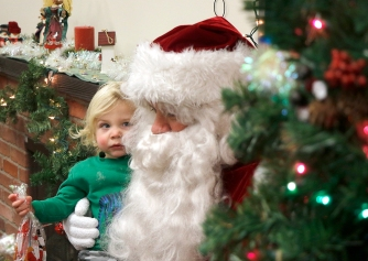 Levi Schrum sits with Santa in the Fort Calhoun Fire Station Saturday at the Soup with Santa event.