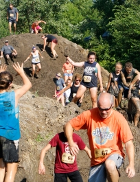 A steep mud hill and ditches filled with water were just a couple of the obstacles that Chris Martens and a crowd of participants maneuver Saturday morning at the Cowboy 5 K.