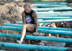 Madyson Ray climbs over plastic pipes while her friends crawl under and through the muddy ditch Washington County Fair Saturday AM