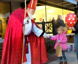 Episcopal Church Deacon Wes Agar dressed as St. Nicholas hands a treat to Sydney Preister.