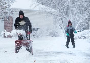 Caiden Brown and his cousin Ava Brown clear the snow from Terri Brown's driveway along 20th street Monday afternoon.