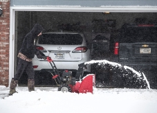 Caiden Brown clears the snow from Terri Brown's driveway along 20th street Monday afternoon.