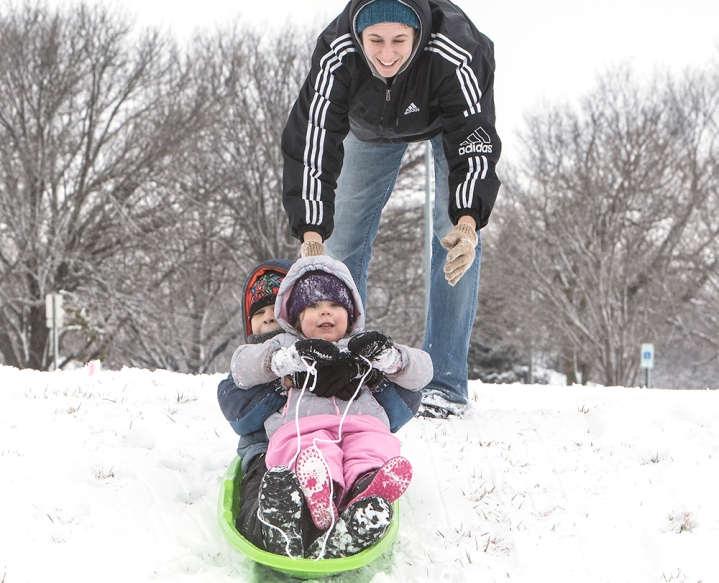 Leigh Hinrichs in background launches son and daughter Theo and Lily on a ride down a gentle slope at Stemmerman Park on Tuesday. This is adventure in the snow for three year old Lily. The family recently moved to Blair from Oklahoma.
