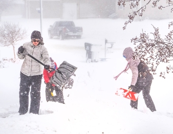 As the wind picks up, Kim Leggot and kids Bredon and Abby clear their driveway in the Deerfield subdivision.